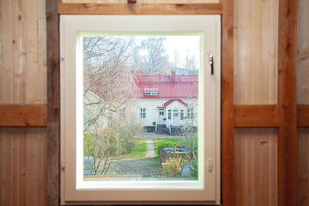 Pihalle päin olevan vintin päätykolmion ikkunasta on näkymä Puu-Raksilaan.